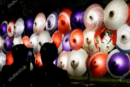 Visitors take photos of traditional umbrella-shaped lanterns being lit up to mark the 100th anniversary of the Meiji Jingu Shinto Shrine in Tokyo . Meiji Jingu, was built to pay tribute to the Emperor Meiji and Empress Shoken in 1920