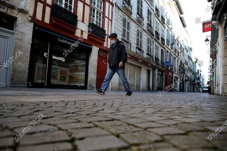 Man walks in an empty street during a nationwide confinement to counter the Covid-19, in Bayonne, southwestern France . France re-imposed a monthlong nationwide lockdown Friday aimed at slowing the spread of the virus, closing all non-essential business and forbidding people from going beyond one kilometer from their homes except to go to school or a few other essential reasons
