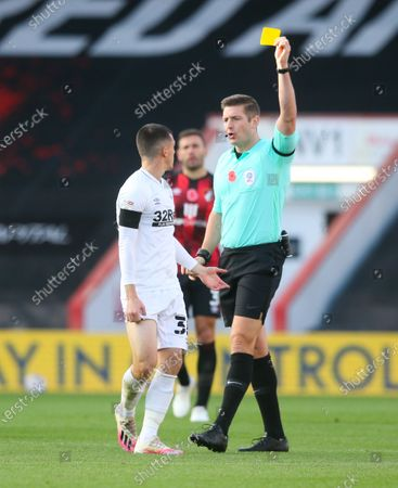 Jason Knight of Derby County is shown a yellow card by referee Rob Jones