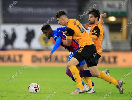 Wilfried Zaha (11) of Crystal Palace is challenged by Maximilian Kilman (49) and Ruben Neves (8) of Wolverhampton Wanderers and
