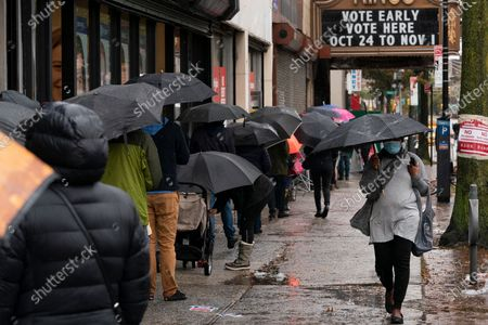 People under umbrellas practice social distancing as they line up for early voting, in the Brooklyn borough of New York. The national election is Nov. 3