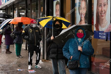 People under umbrellas line up for early voting, in the Brooklyn borough of New York. The national election is Nov. 3