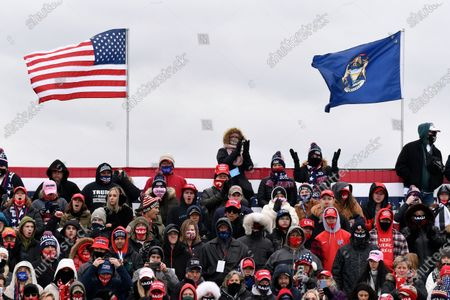 Supporters of President Donald Trump cheer as Housing and Urban Development Secretary Ben Carson takes the stage at a campaign rally held at Oakland County International Airport, in Waterford Township, Mich