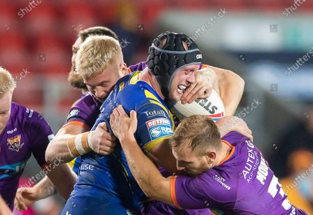 Warrington's Chris Hill is tackled by Huddersfield's Oliver Wilson & Brandon Moore,