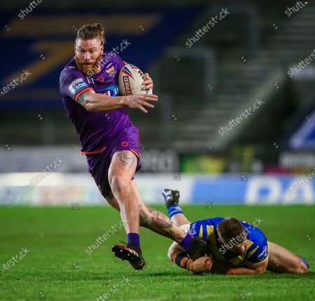 Stock Image of Huddersfield's Chris McQueen escapes the tackle of Warrington's Matthew Davis.