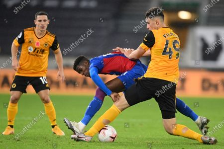 Crystal Palace's Wilfried Zaha, left, challenges for the ball with Wolverhampton Wanderers' Max Kilman during the English Premier League soccer match between Wolverhampton Wanderers and Crystal Palace at the Molineux Stadium in Wolverhampton, England