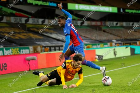 Wolverhampton Wanderers' Rayan Ait-Nouri, bottom, challenges for the ball with Crystal Palace's Wilfried Zaha during the English Premier League soccer match between Wolverhampton Wanderers and Crystal Palace at the Molineux Stadium in Wolverhampton, England