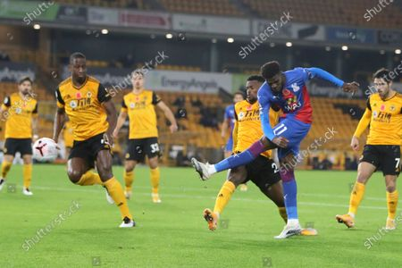 Crystal Palace's Wilfried Zaha, right, takes a shot at goal next to Wolverhampton Wanderers' Ki-Jana Hoever during the English Premier League soccer match between Wolverhampton Wanderers and Crystal Palace at the Molineux Stadium in Wolverhampton, England