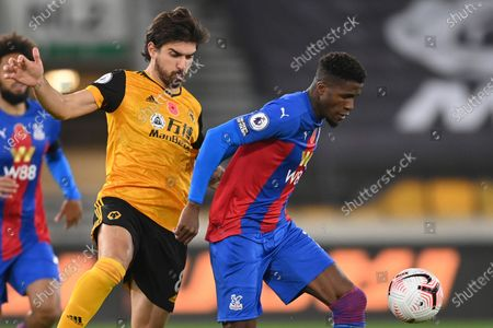 Wolverhampton Wanderers' Ruben Neves, left, challenges for the ball with Crystal Palace's Wilfried Zaha during the English Premier League soccer match between Wolverhampton Wanderers and Crystal Palace at the Molineux Stadium in Wolverhampton, England
