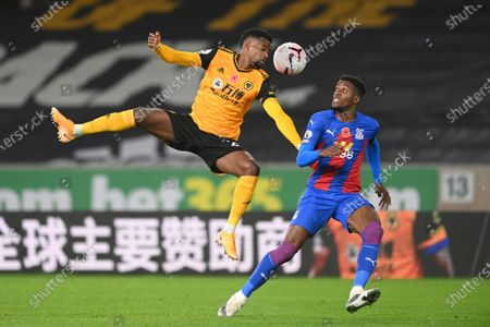 Wolverhampton Wanderers' Nelson Semedo, left, challenges for the ball with Crystal Palace's Wilfried Zaha during the English Premier League soccer match between Wolverhampton Wanderers and Crystal Palace at the Molineux Stadium in Wolverhampton, England