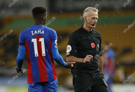 Stock Photo of Referee Martin Atkinson speaks to Wilfried Zaha of Crystal Palace during the English Premier League match between Wolverhampton Wanderers and Crystal Palace in Wolverhampton, Britain 30 October 2020.