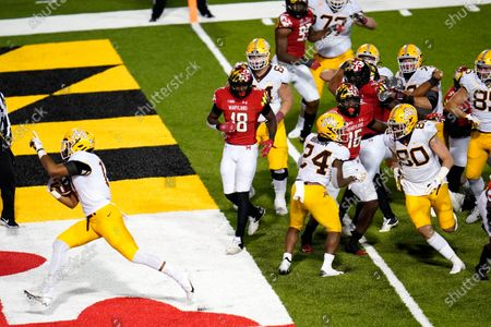 Minnesota wide receiver Seth Green, left, scores a touchdown run against Maryland during overtime of an NCAA college football game, in College Park, Md. Maryland won 45-44 in overtime