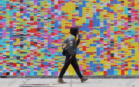 A passerby walks past the art installation called 'Wall Of Lies', which documents President Trump's lies during his time in office, is erected in SoHo
