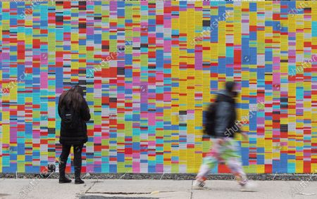 Passersby in front of the art installation called 'Wall Of Lies', which documents President Trump's lies during his time in office, is erected in SoHo