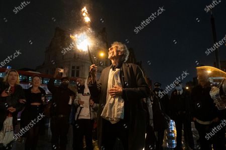 Stock Picture of PIERS CORBYN is seen practicing fire breathing in front of demonstrators attending an anti Covid-19 street party in Camden Town, North London. The event was held in support of the hospitality industry who have operated under strict lockdown rules. Police officers did not intervene in the demonstration.