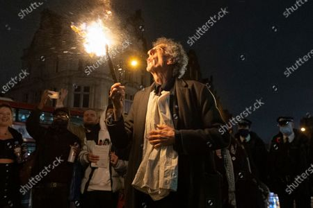 Stock Image of PIERS CORBYN is seen practicing fire breathing in front of demonstrators attending an anti Covid-19 street party in Camden Town, North London. The event was held in support of the hospitality industry who have operated under strict lockdown rules. Police officers did not intervene in the demonstration.