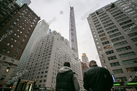 A crane perched near the top of a midtown high-rise was left spinning from the strong winds Thursday evening, city officials said, forcing four blocks in Manhattan to close down as debris came falling from above.