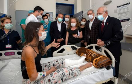 Kemal Kilicdaroglu, the leader of Turkey's main opposition Republican People's Party, right, speaks with a survivor rescued from the debris of a collapsed building, in Izmir, Turkey, . Three young children and their mother were rescued alive from the rubble of a collapsed building in western Turkey on Saturday, some 23 hours after a powerful earthquake in the Aegean Sea killed several people and injured more than 800 others
