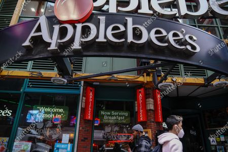 A man wearing face mask walks past the Applebee's Times Square branch in New York City.  Applebee's Neighborhood Grill is expected to permanently shut down  15 branches during the fourth quarter, franchisor Dine Brands Global alerted investors Wednesday.