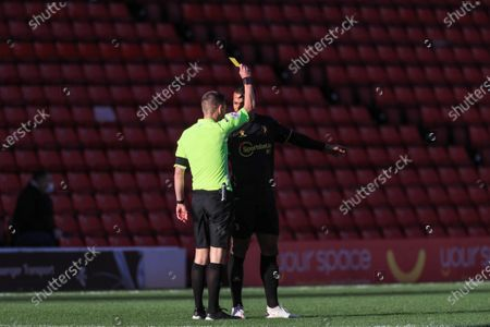 referee Matthew Donohue gives William Troost-Ekong (5) of Watford a yellow card