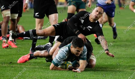 Australia's Noah Lolesio, bottom, scores his team's first try as New Zealand's Aaron Smith attempts a tackle during the Bledisloe rugby test between the All Blacks and the Wallabies at Stadium Australia, Sydney, Australia