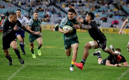 Stock Picture of Australia's Noah Lolesio, centre, runs past New Zealand's Richie Mo'unga, right, and Aaron Smith left, to score his team's first try during the Bledisloe rugby test between the All Blacks and the Wallabies at Stadium Australia, Sydney, Australia