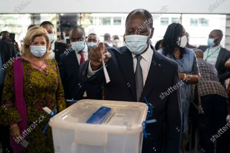 Ivory Coast President Alassane Ouattara casts his vote as his wife Dominique Ouattara, left, looks on at a polling station during presidential elections in Abidjan, Ivory Coast, . Tens of thousands of security forces are deployed across Ivory Coast on Saturday as the leading opposition parties boycotted the election, calling President Ouattara's bid for a third term illegal