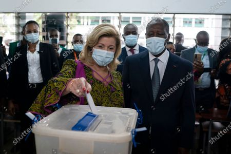 Dominique Ouattara casts her vote as her husband, the Ivory Coast President Alassane Ouattara, right, looks on at a polling station during presidential elections in Abidjan, Ivory Coast, . Tens of thousands of security forces are deployed across Ivory Coast on Saturday as the leading opposition parties boycotted the election, calling President Ouattara's bid for a third term illegal