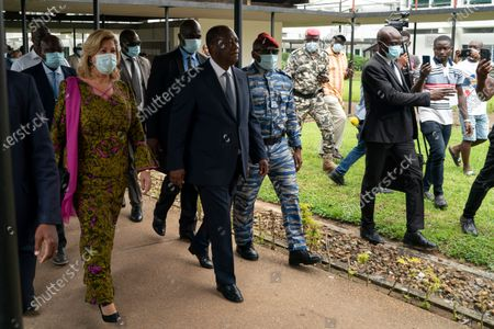 Ivory Coast President Alassane Ouattara, center, and his wife Dominique Ouattara, left, leave after voting in a polling station during presidential elections in Abidjan, Ivory Coast, . Tens of thousands of security forces deployed across Ivory Coast on Saturday as the leading opposition parties boycotted the election, calling President Ouattara's bid for a third term illegal