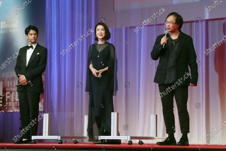 Japanese film director Koji Fukada, right, delivers a speech as actor Win Morisaki and actress Mariko Tsutsui listen during the opening ceremony of the Tokyo International Film Festival in Tokyo