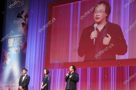 Japanese film director Koji Fukada, right, delivers a speech as actor Win Morisaki and actress Mariko Tsutsui, listen during the opening ceremony of the Tokyo International Film Festival in Tokyo