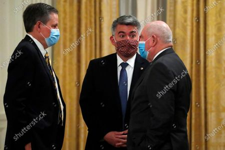 """Sen. Steve Daines, R- Mont., left, Sen. Cory Gardner, R-Colo., center, and Agriculture Secretary Sonny Perdue talk before a signing ceremony for H.R. 1957, """"The Great American Outdoors Act,"""" in the East Room of the White House in Washington. The two Republicans have trumpeted their work on the measure but that hasn't stopped their Democratic opponents from questioning their conservation credentials"""