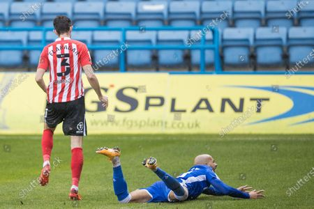 Tom Flanagan, Defender with Sunderland AFC (3) & Jordan Graham, Midfielder with Gillingham (10) who is appealing to Anthony Da Costa (Assistant Referee) from the ground during the EFL Sky Bet League 1 match between Gillingham and Sunderland at the MEMS Priestfield Stadium, Gillingham