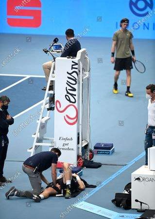 Medical staff helps  Kevin Anderson of South Africa on the ground while Andrey Rublev of Russia (R) watches at the Erste Bank Open ATP tennis tournament in Vienna, Austria, 31 October 2020.
