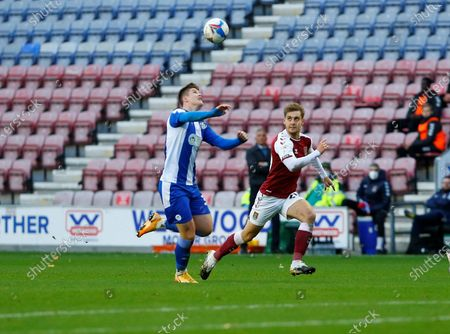 Northampton Town Defender Michael Harriman (2)and Wigan Athletic defender Tom Pearce (3)chase down the ball during the EFL Sky Bet League 1 match between Wigan Athletic and Northampton Town at the DW Stadium, Wigan