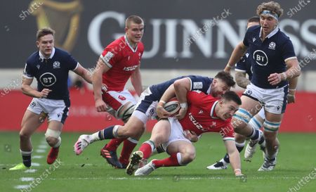 Stock Photo of Josh Adams of Wales (C) is being tackled by Ali Price of Scotland (C-L) during the Rugby Six Nations match between Wales and Scotland in Cardiff, Britain, 31 October 2020.