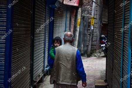 A man carrying a kid walks past closed shops during the shutdown in Kashmir. A shutdown was observed across the Kashmir valley to protest against India's new laws that allow Indians to buy land in the region. The shutdown call was made by a separatist group headed by Mirwaiz Umar Farooq.