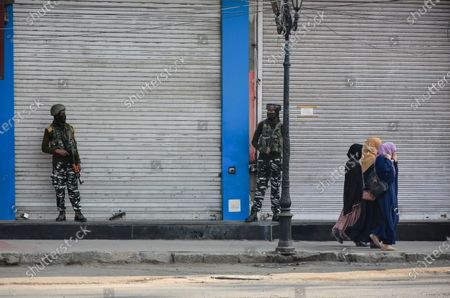 Kashmir women walk past paramilitary troopers standing on guard during the shutdown in Kashmir. A shutdown was observed across the Kashmir valley to protest against India's new laws that allow Indians to buy land in the region. The shutdown call was made by a separatist group headed by Mirwaiz Umar Farooq.
