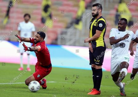 Stock Photo of Al-Ahli's goalkeeper Yasser Al-Mosailem (2-L) tries to save the ball during the Saudi Professional League soccer match between Al-Ittihad and Al-Ahli at King Abdullah Sport City Stadium, 30 kilometers north of Jeddah, Saudi Arabia, 31 October 2020.
