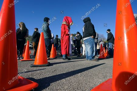 Adam Fogerty, center, wears a costume on Halloween, as he stands in line with others to vote early, at the Douglas County Election Commission office in Omaha, Neb