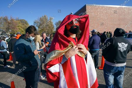 Adam Fogerty wears a costume on Halloween, as he stands in line with others to vote early, at the Douglas County Election Commission office in Omaha, Neb