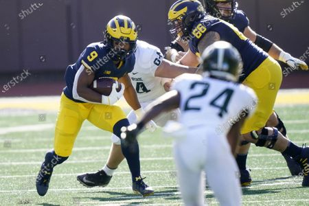 Michigan running back Chris Evans (9) looks for a hole during the first half of an NCAA college football game against Michigan State, in Ann Arbor, Mich