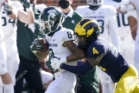Michigan State wide receiver Jalen Nailor (8) is tackled by Michigan defensive back Vincent Gray (4) after a catch during the first half of an NCAA college football game, in Ann Arbor, Mich