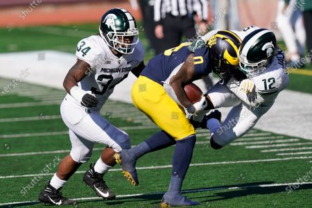 Michigan wide receiver Giles Jackson (0) is pulled out of bounds by Michigan State cornerback Chris Jackson (12) during the second half of an NCAA college football game, in Ann Arbor, Mich