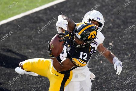 Iowa wide receiver Brandon Smith (12) catches a touchdown pass in front of Northwestern defensive back Cameron Ruiz during the first half of an NCAA college football game, in Iowa City, Iowa
