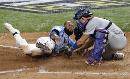 Tampa Bay Rays baserunner Manuel Margot (L) is tagged out by Los Angeles Dodgers catcher Austin Barnes (R) as he tried to steal home plate in the bottom of the fourth inning of Major League Baseball's World Series Game five at Globe Life Field in Arlington, Texas, USA, 25 October 2020. The best-of-seven series is tied 2-2.