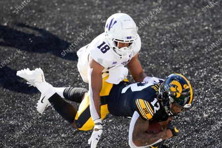 Iowa wide receiver Brandon Smith (12) catches a 7-yard touchdown pass ahead of Northwestern defensive back Cameron Ruiz (18) during the first half of an NCAA college football game, in Iowa City, Iowa