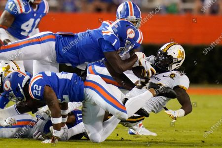 Missouri running back Larry Rountree III, right, is stopped by the Florida defense, including linebacker Brenton Cox Jr. (1) and defensive back Brad Stewart Jr., back, during the first half of an NCAA college football game, in Gainesville, Fla
