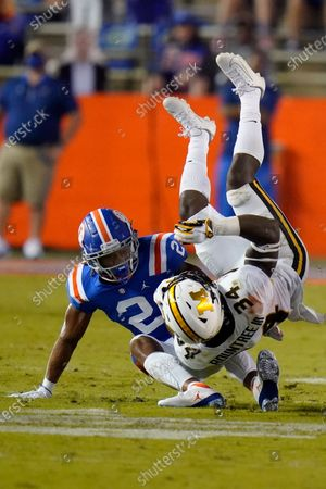 Missouri running back Larry Rountree III (34) is upended by Florida defensive back Brad Stewart Jr. (2) during the first half of an NCAA college football game, in Gainesville, Fla