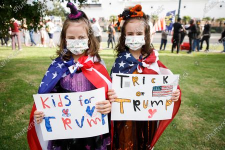 Twin sisters Isabella and Vanessa Statkov (R) pose with signs of support for US President Donald J. Trump while wearing their Halloween costumes during a rally in Beverly Hills, California, USA, 31 October 2020. Thousands of supporters with many in costumes gathered for the event.